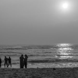 Chennai,India,Jan 21 2018: Black and white silhouette of group of friends and family having peaceful and leisure time at Marine beach near the shore.